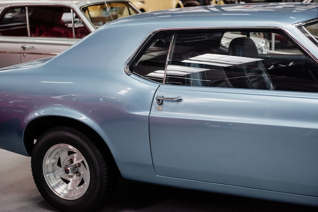 Widok z boku rzadkiego niebieskiego samochodu na wystawie samochodowej
