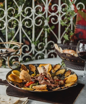 Widok z boku saj kebap z jagnięcymi żebrami ziemniaków kolorowe papryki i bakłażany na drewnianej desce na stole