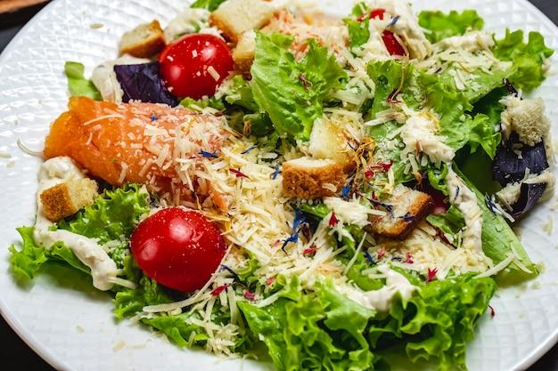 Widok z boku sałatka cezar z wędzonym łososiem rusk sosem pomidorowym sałata i parmezanem na talerzu