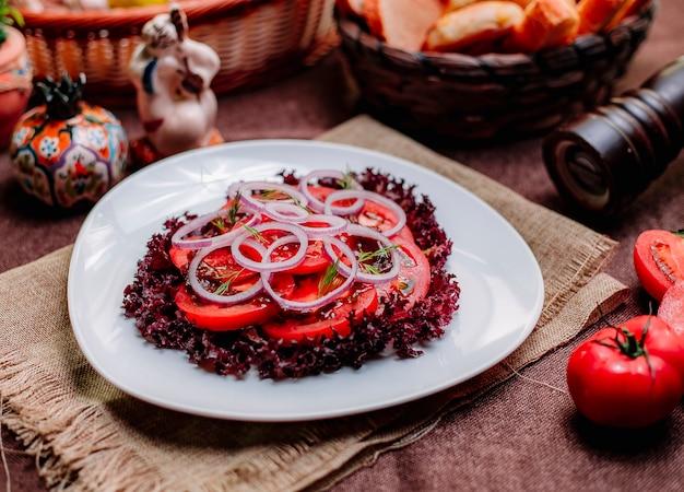 Widok z boku sałatka pomidorowa pokrojone pomidory z czerwoną cebulą i sałatą na talerzu