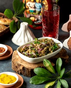 Widok z boku sałatki z kapusty z marynowanym pieprzem i czerwoną cebulą w misce