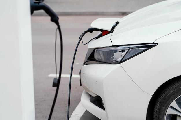 Widok z boku samochodu ładowanego na stacji ładowania pojazdów elektrycznych