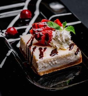 Widok z boku sernik z bitą czekoladą, miętą truskawkową i wiśnią na talerzu