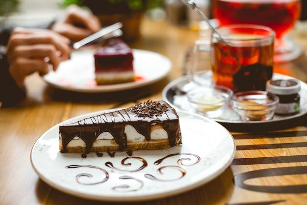 Widok z boku sernika pokryte sosem czekoladowym na talerzu