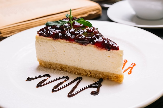 Widok z boku sernika z galaretką wiśniową na górze na białym talerzu