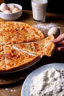 Widok z boku serowa pizza z jajkami szklanka mleka i mąki na stole