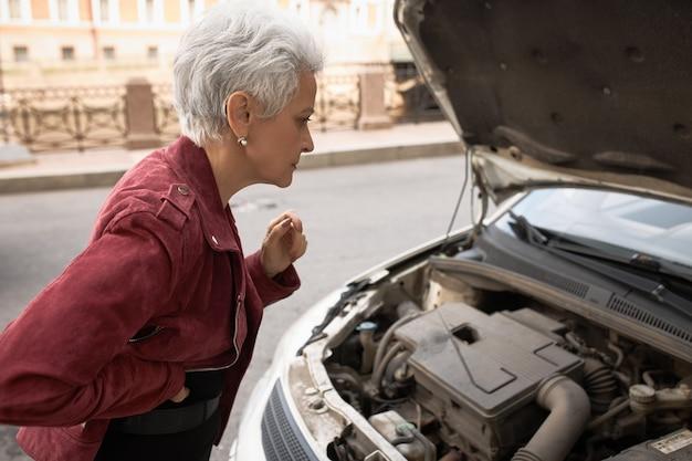Widok z boku sfrustrowanej kobiety w średnim wieku stojącej przy swoim samochodzie z otwartą maską, zaglądającej do środka i próbującej dowiedzieć się, w czym tkwi problem.
