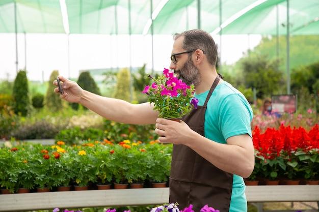 Widok z boku siwowłosego ogrodnika robiącego selfie z petunią