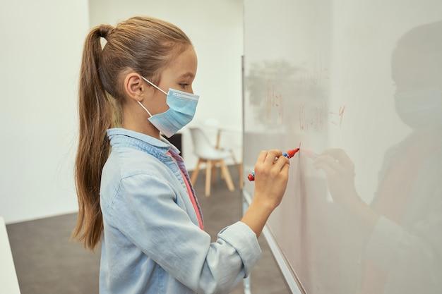 Widok z boku skupionej małej uczennicy noszącej maskę ochronną podczas pisania pandemii koronawirusa