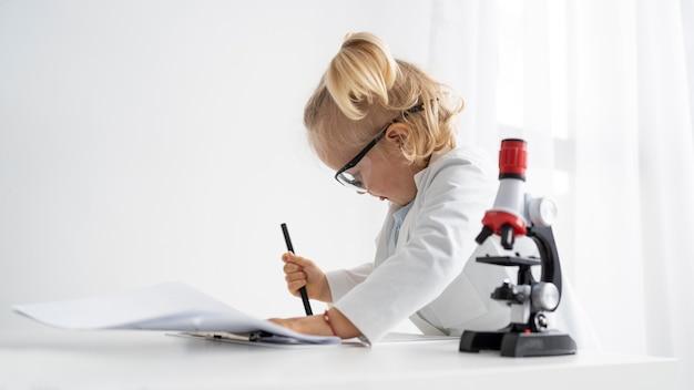 Widok z boku ślicznego malucha z fartuchem laboratoryjnym i mikroskopem