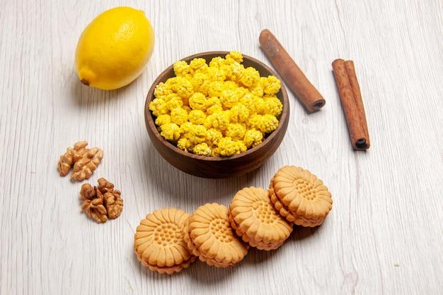 Widok z boku słodycze orzechy cytrynowe ciasteczka laski cynamonu miska żółtych cukierków na białej powierzchni