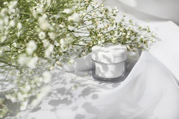 Widok z boku słoika z białym kremem. kosmetologia organiczna, koncepcja botaniczna kosmetyki naturalne. produkt do pielęgnacji skóry kobiet. plastikowy pojemnik na balsam do twarzy i ciała oraz kompozycja liści