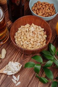 Widok z boku słonych przekąsek orzeszków ziemnych w drewnianej misce z migdałami i kuflem piwa na rustykalnym drewnie