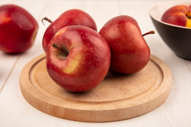 Widok z boku smaczne czerwone jabłka na drewnianej desce kuchennej na białej drewnianej powierzchni