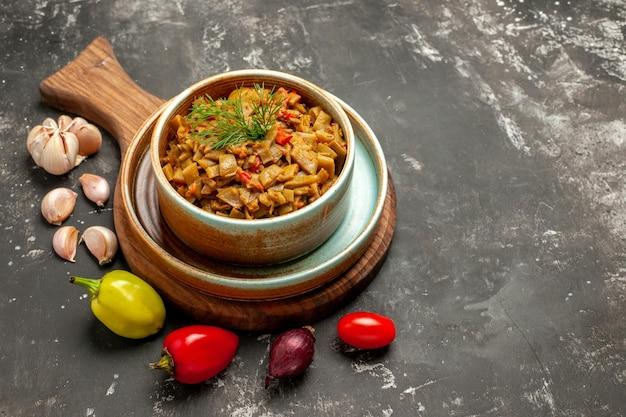 Widok z boku smaczne danie smaczne danie na desce czosnek cebula papryka na ciemnym stole