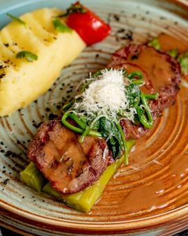 Widok z boku smażone mięso na szparagach z puree ziemniaczanym i ziołami w talerzu