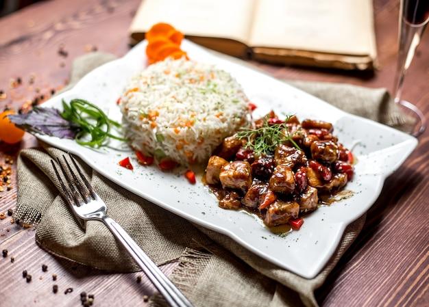Widok z boku smażone mięso w sosie z suszonymi owocami i ryżem