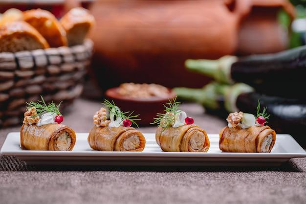 Widok z boku smażone rolki bakłażana z orzechami i czosnkiem ozdobione koperkiem na stole