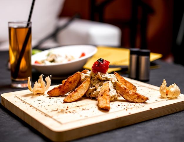 Widok z boku smażonej piersi z kurczaka w sosie serowym z domowymi ziemniakami i smażonym pomidorem na desce