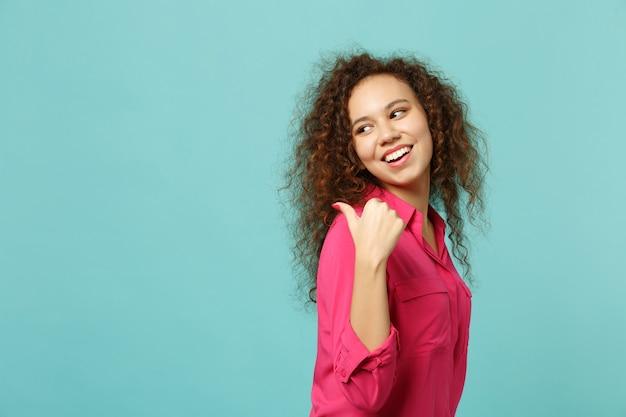 Widok z boku śmieszne afrykańskie dziewczyny w ubranie patrząc wstecz, wskazując kciukiem na bok na białym tle na tle niebieskiej ściany turkus w studio. koncepcja życia szczere emocje ludzi. makieta miejsca na kopię.
