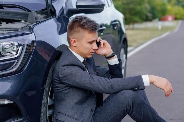 Widok z boku smutny biznesmen za pomocą smartfona siedzi na drodze w pobliżu zepsutego samochodu