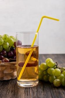 Widok z boku soku winogronowego w szkle i winogron w koszu i na powierzchni drewnianych i białym tle