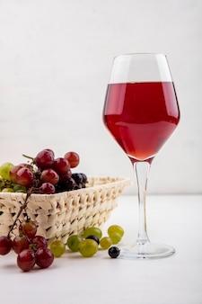 Widok z boku soku z czarnych winogron w kieliszek i kosz winogron z jagodami winogron na białym tle