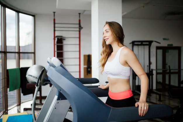 Widok z boku sportowej kobiety ćwiczeń na bieżni w siłowni
