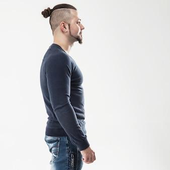 Widok z boku - sportowiec - kulturysta w dżinsach i koszulce na jasnej ścianie. zdjęcie ma puste miejsce na tekst