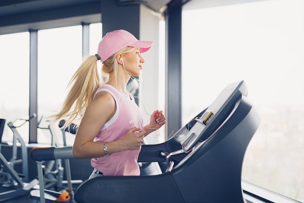 Widok z boku sportowy blond kobieta w różowej czapce, ćwiczenia na bieżni w siłowni
