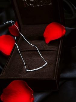 Widok z boku srebrnego naszyjnika z kryształem swarovskiego na czarnej ścianie
