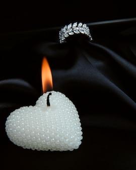 Widok z boku srebrnego pierścionka z brylantami i płonącą dekoracyjną świecą w kształcie serca na czarnej ścianie