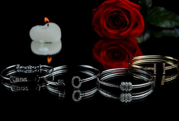 Widok z boku srebrnych bransolet z brylantami na czarnej ścianie