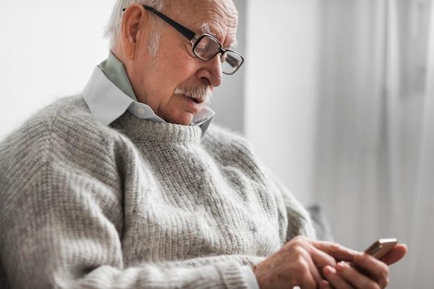 Widok z boku starego człowieka w domu opieki za pomocą smartfona