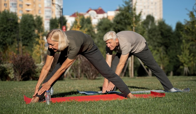 Widok z boku starsza para praktykujących jogę na świeżym powietrzu