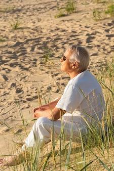 Widok z boku starszego mężczyzny odpoczywającego w słońcu na plaży