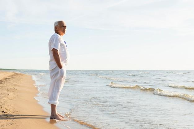 Widok z boku starszego mężczyzny, podziwiając widok na plaży