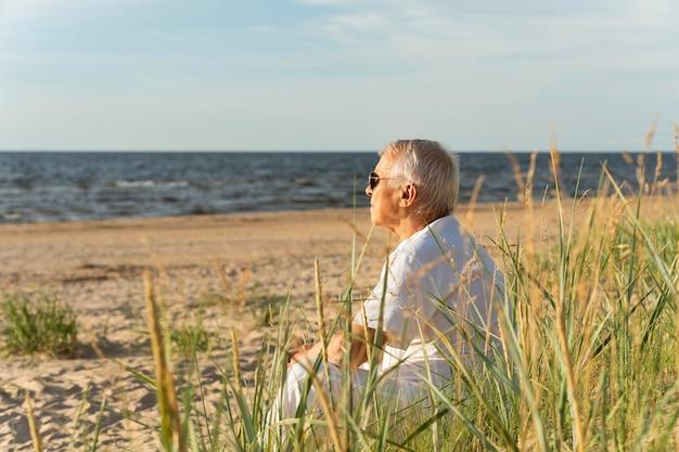 Widok z boku starszego mężczyzny spędzającego czas na plaży