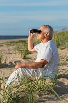 Widok z boku starszego mężczyzny z lornetką, podziwiającego plażę