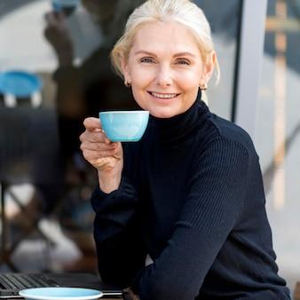 Widok z boku starszej kobiety biznesu, ciesząc się kawą na zewnątrz podczas pracy