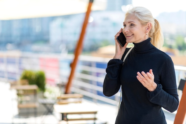 Widok z boku starszej kobiety biznesu na zewnątrz na telefon