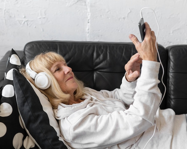 Widok z boku starszej kobiety, słuchanie muzyki w domu na słuchawkach