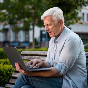 Widok z boku starszy mężczyzna na zewnątrz na ławce z laptopem