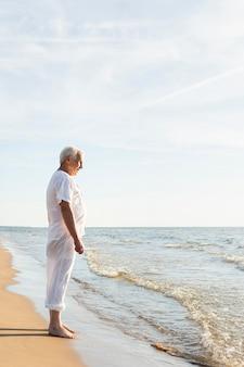 Widok z boku starszy mężczyzna odpoczywa podziwiając widok na plażę