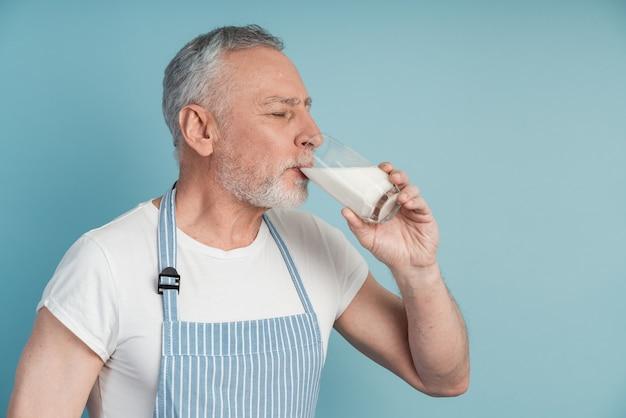 Widok z boku, starszy mężczyzna pije mleko i zamyka oczy