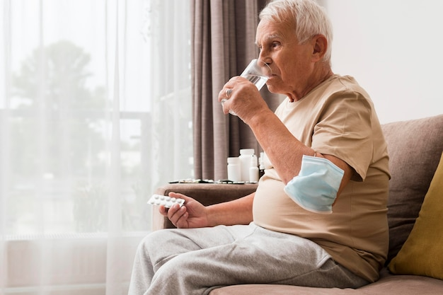 Widok z boku stary człowiek biorąc pigułkę