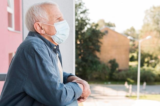 Widok z boku stary człowiek ubrany w maskę medyczną