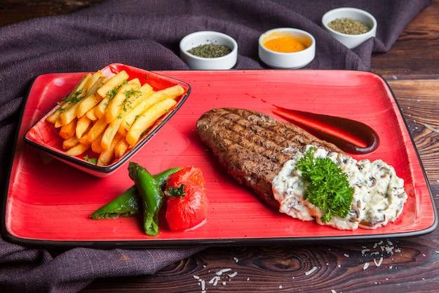 Widok z boku stek ze smażonym sosem ziemniaczanym, przyprawy na czerwonym talerzu