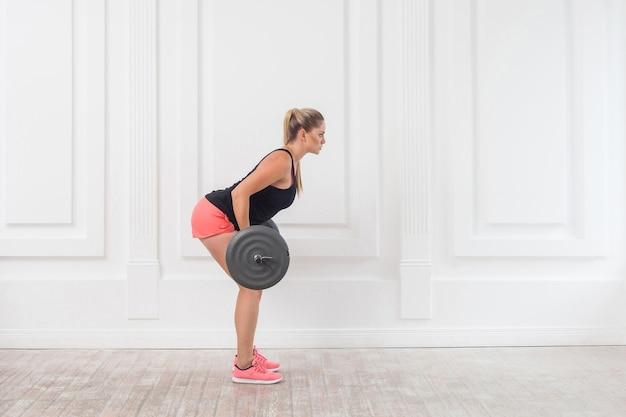Widok z boku stężenie portret kobiety młode sportowe piękne kulturysta w różowe spodenki i czarny top robi przysiady i ćwiczenia mięśnia pośladkowego na siłowni ze sztangą na białej ścianie. wnętrz