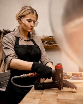 Widok z boku stolarza kobieta z zszywaczem pneumatycznym w studio